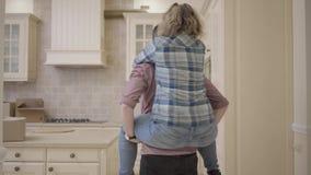 De gebaarde man draagt mooie vrouwenzitting op zijn rug in de keuken en zet haar op de lijst De vrouw koestert haar echtgenoot stock video