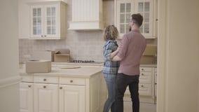 De gebaarde man en de mooie vrouw gaan de keuken in, houdend handen De mens zet zijn vrouw op de lijst De vrouw koestert haar ech stock videobeelden
