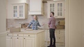 De gebaarde man en de mooie vrouw gaan de keuken in, houdend handen Zet het mensen dragende vakje en het op lijst De vrouw koeste stock videobeelden