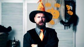 De gebaarde man in het heksen` s kostuum toont grimassen Een gebaarde mens in een oranje hoed toont grimassen op Halloween-vakant stock footage