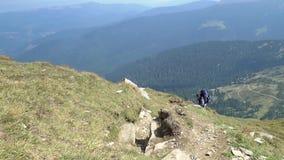 De gebaarde mens beklimt de berg stock footage