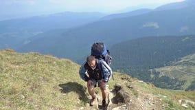 De gebaarde mens beklimt de berg, close-up stock footage