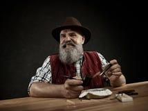 De gebaarde mens belemmert de tabak in pijp stock fotografie