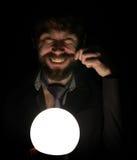 De gebaarde mens in dark, die voor een lamp houden, drukt verschillende emoties uit het tollen van zijn snor met uw Royalty-vrije Stock Afbeeldingen