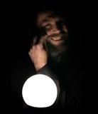De gebaarde mens in dark, die voor een lamp houden, drukt verschillende emoties uit het tollen van zijn snor met uw Stock Afbeeldingen