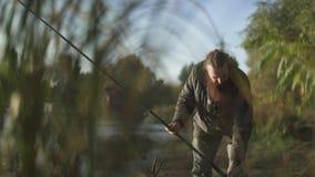 De gebaarde mens die met een hengel vissen, verlaat zijn staaf op de rivierbank en gaat weg De visser is bezig geweest met een ho stock video