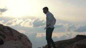 De gebaarde mens in een wit overhemd die zich bovenop een berg bevinden tuurt bij de wolken Jonge modieuze kereltribune op de hog stock video