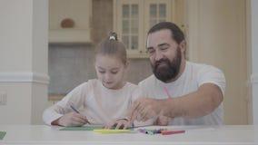 De gebaarde mens en het meisje trekken met tellers thuis zittend bij de lijst Vader die zijn dochter helpen te trekken, steunen stock video