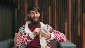 De gebaarde mens gebruikt een telefoon stock video