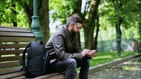 De gebaarde mens gebruikt de telefoon in het park op de bank stock footage