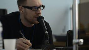 De gebaarde mens in glazen spreekt in de microfoon stock video
