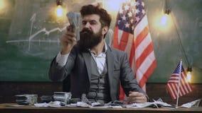 De gebaarde mens houdt een bos van dollars tegen de achtergrond van Amerikaanse vlag die sterk U vertegenwoordigen S economie rij stock footage