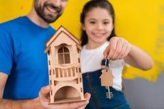 De gebaarde mens houdt stuk speelgoed het blokhuis in zijn handen en meisje sleutels aan huis houdt royalty-vrije stock afbeelding