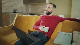 De gebaarde mens koffie hebben of de thee die pauzeert terwijl het gebruiken van laptop terwijl thuis 4k lengte stock video