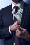 De gebaarde mens in kostuum verwijdert geld aan zijn zak Royalty-vrije Stock Fotografie
