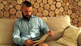 De gebaarde mens las een boek stock video