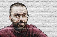 De gebaarde mens met dichte scheerbeurt schilderde op muur Royalty-vrije Stock Foto