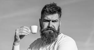 De gebaarde mens met espressomok, drinkt koffie Koffie gastronomisch concept Mens met baard en snor op strikte gezichtsdranken royalty-vrije stock fotografie