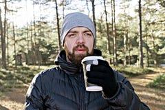 De gebaarde mens met haalt kop van koffie weg lopend in bos royalty-vrije stock foto