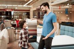 De gebaarde mens met jonge jongen kiest kleur op kleurenpalet Het selecteren van kleur van matras op de gids van het kleurenpalet Royalty-vrije Stock Afbeelding
