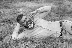 De gebaarde mens met madeliefjebloemen in baard legt op weide, helling op hand, grasachtergrond Kerel met binnen boeket van madel royalty-vrije stock afbeeldingen