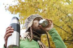 De gebaarde mens in wol breide hoed drinkt zorgvuldig hete thee of koffie van mok, bodem zijaanzicht, achtergrond van geel de her stock afbeelding
