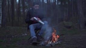 De gebaarde mens zit in het bos dichtbij vuur en zette drank in een kop van thermosflessen Brutale ongeschoren kerel die door rus stock video