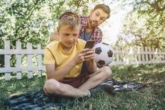 De gebaarde mens zit op de rug van zijn zoon, wil hij footbll spel met kind spelen Het jonge geitje is niet geinteresseerd in dat royalty-vrije stock fotografie