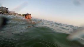 De gebaarde mens zwemt in het overzees stock videobeelden