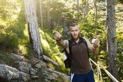 De gebaarde modieuze wandelaarmens die gps navigatie voor het plaatsen gebruiken bij de berg sleept en denkt waar te gaan technol Royalty-vrije Stock Afbeelding