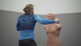 De gebaarde professionele mens met atletisch lichaam en het blonde lange haar maken sidekick aan een ledenpop tot van de loodjesd stock footage
