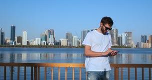 De gebaarde reiziger die in zonnebril kaartjes online op telefoon boeken verbond met 4G Internet lopend met koffiestraten van stock footage