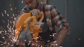De gebaarde sterke werktuigkundige die elektro hoekige malende machine met behulp van bij fabriek, vonken vliegt apart Het werk i stock videobeelden
