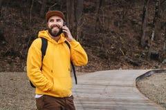 De gebaarde toerist van de hipstermens in geel hoodie en GLB bevindt zich in openlucht, sprekend op mobiele telefoon Glimlachende royalty-vrije stock foto's