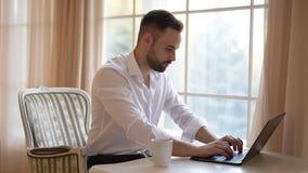 De gebaarde zakenman drinkt koffie en typt op een toetsenbord van laptop stock videobeelden