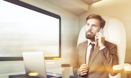 De gebaarde zakenman spreekt aan de gang op zijn mobiel, gestemd Stock Foto
