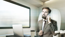 De gebaarde zakenman spreekt aan de gang op zijn mobiel, gestemd Stock Afbeeldingen