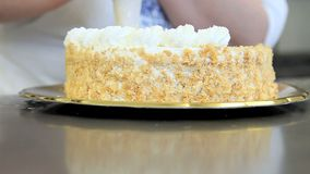 De gebakjechef-kok bereidt de cake met slagroom voor stock videobeelden