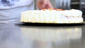 De gebakjechef-kok bereidt fruitcake met slagroom voor stock footage