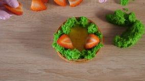 De gebakjechef-kok maakt minicake met room en aardbeiplakken stock videobeelden