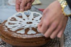 De gebakjechef-kok verfraait een cake royalty-vrije stock afbeelding