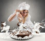 De gebakjekok bereidt een cake voor Royalty-vrije Stock Afbeeldingen
