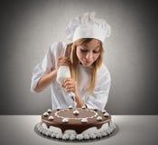 De gebakjekok bereidt een cake voor Stock Foto's