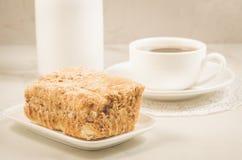 De gebakjes en de kop van koffie/gebakjes en koffie vormen op een witte lijst tot een kom Selectieve nadruk stock afbeelding