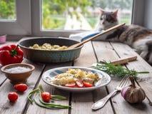 De gebakken bloemkool in gekruide eieren en krsany groenten op een oude houten lijst, op de achtergrond ligt een kat bij het vens royalty-vrije stock foto's