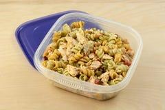 De gebakken salade van zalmdeegwaren in plastic opslagcontainer stock foto