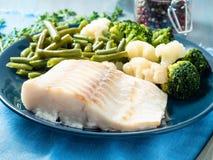 De gebakken van de overzeese filet vissenkabeljauw met groenten op blauwe plaat, blauw Na royalty-vrije stock foto's