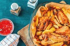 De gebakken vleugels van Turkije met aardappelstukken in een vierkante bakselschotel op een turkooise keukenlijst met saus en kru royalty-vrije stock afbeeldingen