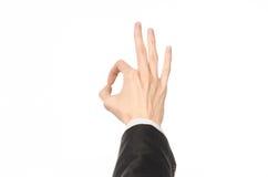 De gebaren en de Zaken als thema hebben: de zakenman toont handgebaren met een eerste-persoon in een zwart kostuum op een witte g Royalty-vrije Stock Foto