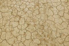 De gebarsten, droge aarde is geel Een woestijn zonder water Dorre grond Dorst voor vochtigheid op een futloze ruimte Ecologische  stock afbeeldingen
